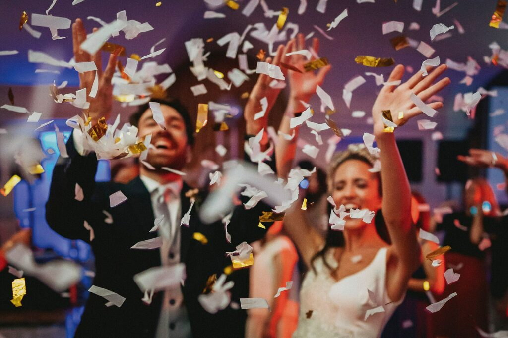 the bride and groom showered with confetti while cutting the wedding cake