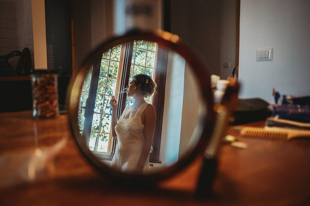 the bride smokes a cigarette before leaving the house to go to the funny wedding at il conventino