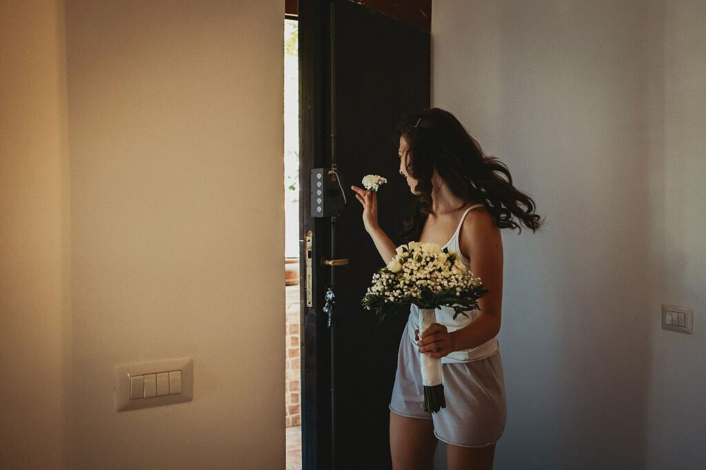 sister of the bride holding the flower bouquet during bride getting ready