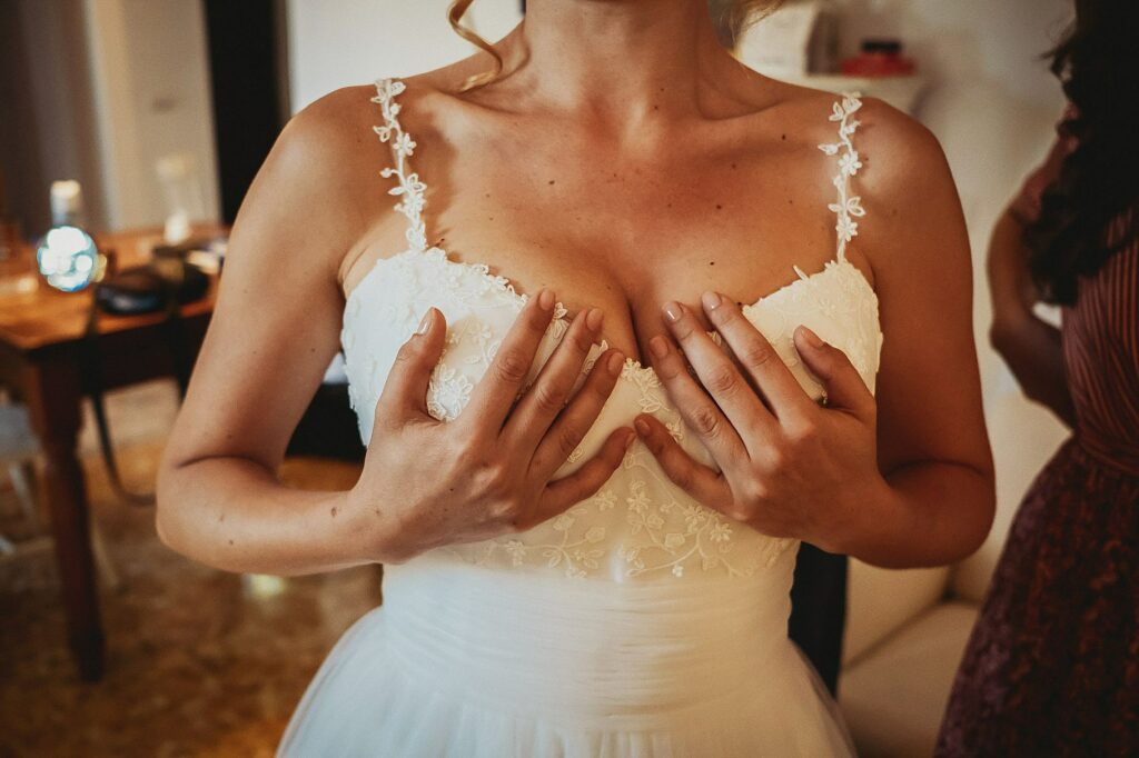 bride holds her breast with her hands while wearing the wedding dress