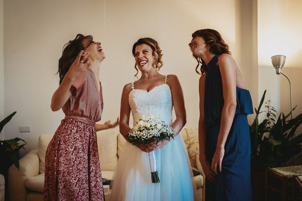 bride and sisters have fun posing for a family photo before leaving for the wedding at il conventino