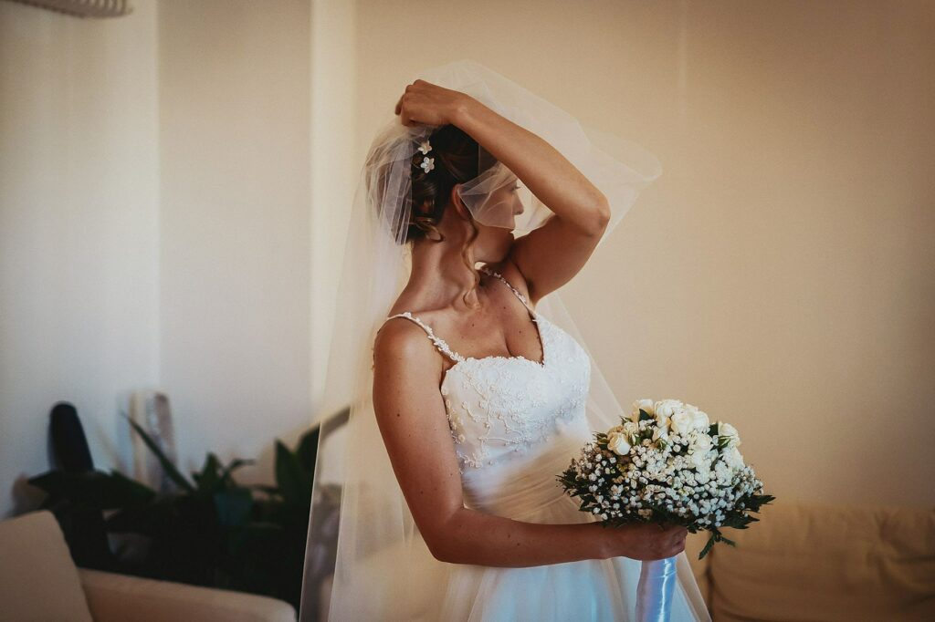 the bride adjusts her veil before leaving the house to go to the wedding at il conventino in mentana