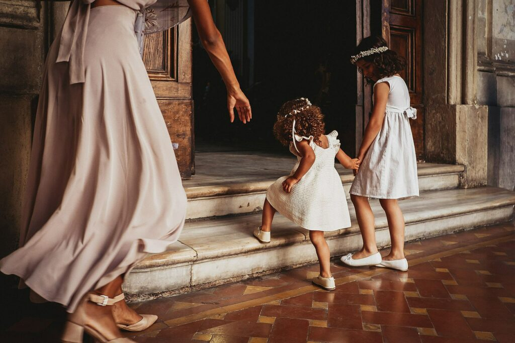 little bridesmaids walk hand in hand into the church of santissime stimmate di san francesco in rome