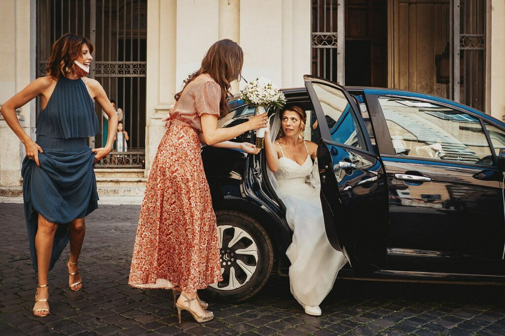 bride arrives in front of the church of santissime stimmate di san francesco and gets out of the car helped by bridesmaid