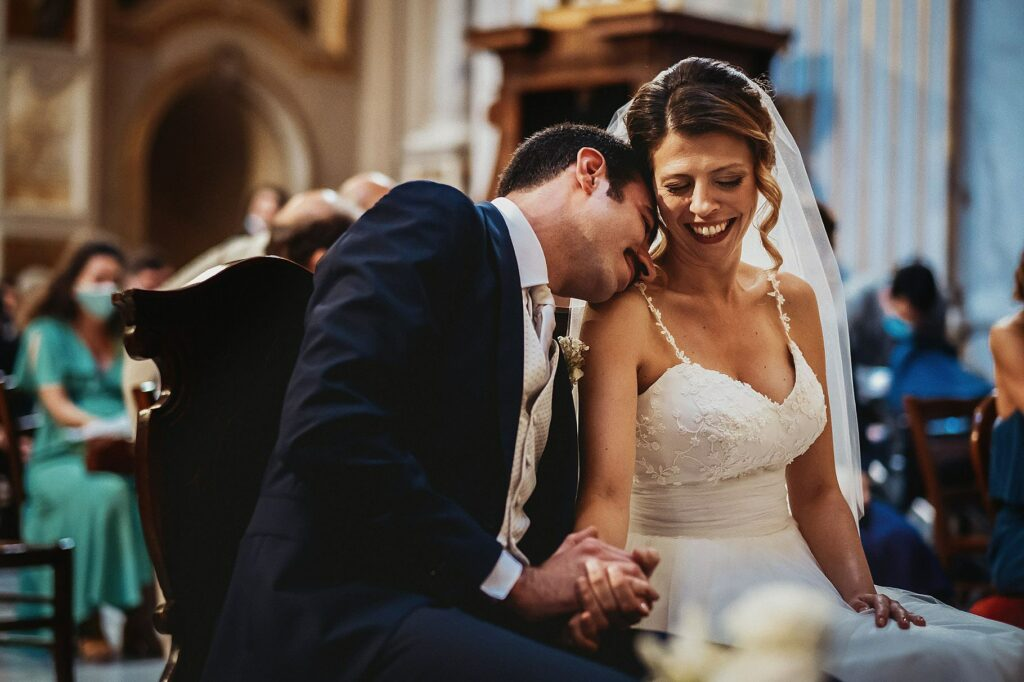 bride and groom in a moment of tenderness during the ceremony at santissime stimmate di san francesco