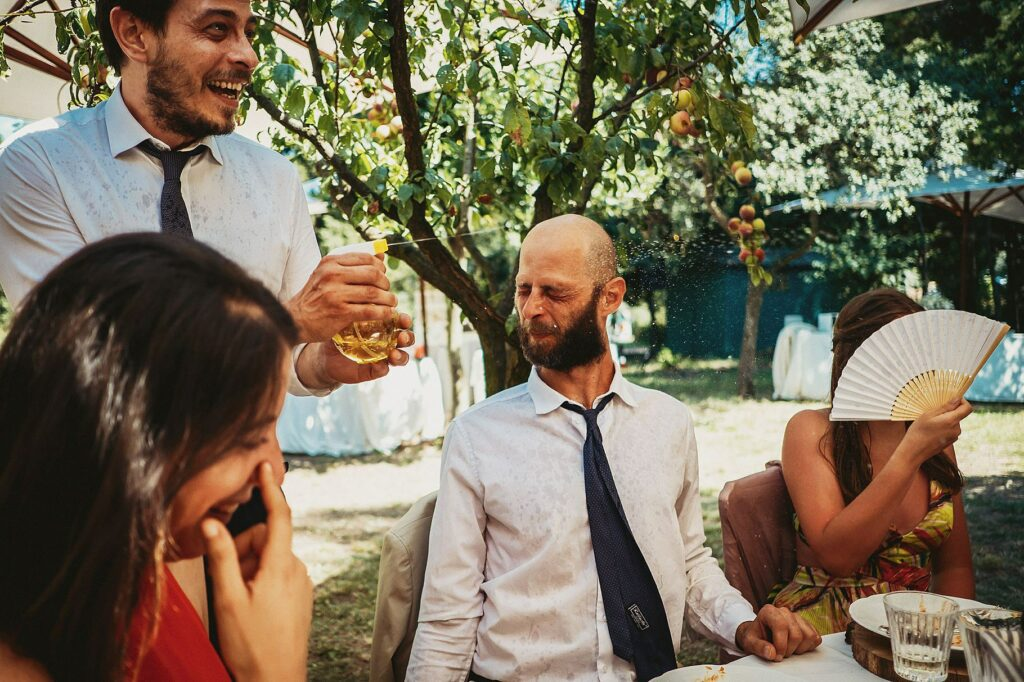 the guests have fun with water guns during the wedding at il conventino