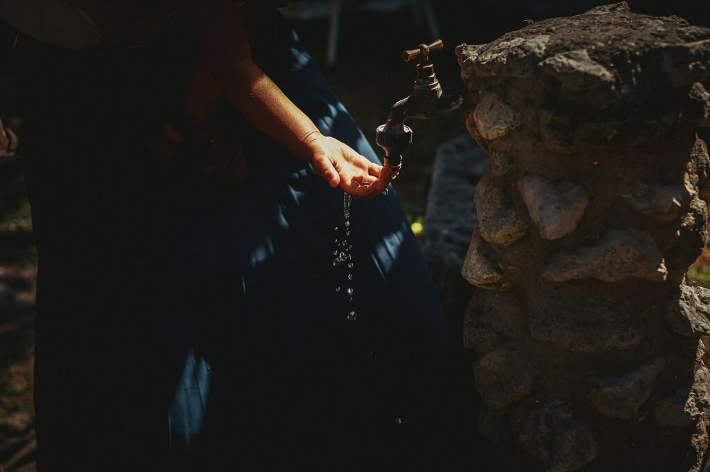 detail of the hand of a child playing with water at the wedding at il conventino