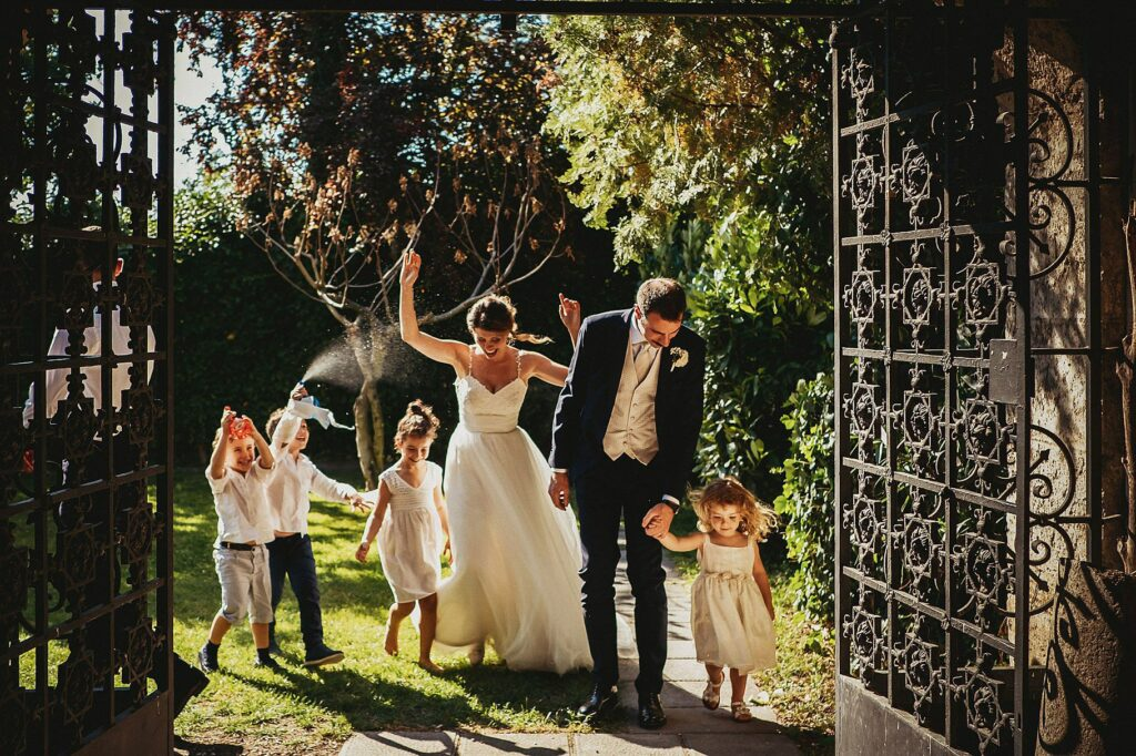 bride and groom with children and water pistols as they enter the cloister of Il Conventino to cut the wedding cake