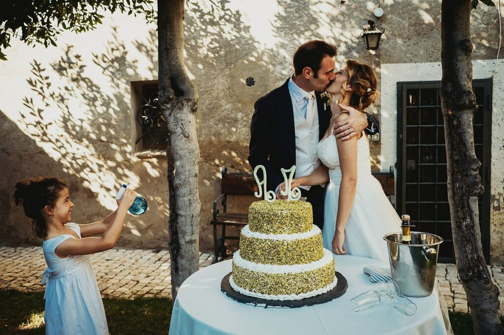 the bride and groom kiss at cake cutting in the cloister of Il Conventino while a little girl tries to wet them with a water gun
