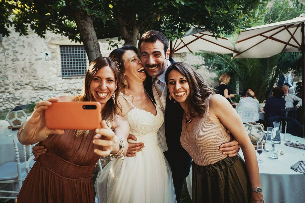 spouses and guests taking a selfie at the wedding dinner at il conventino