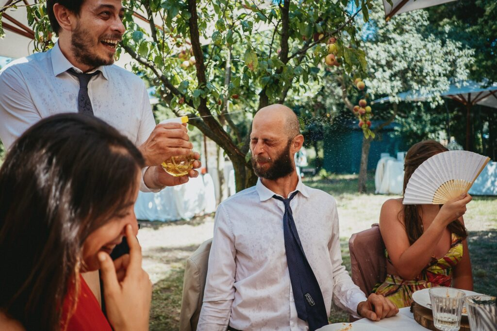 wedding guests having fun with water guns at the reception they will contact and book a photographer in italy to have similar images for their own wedding