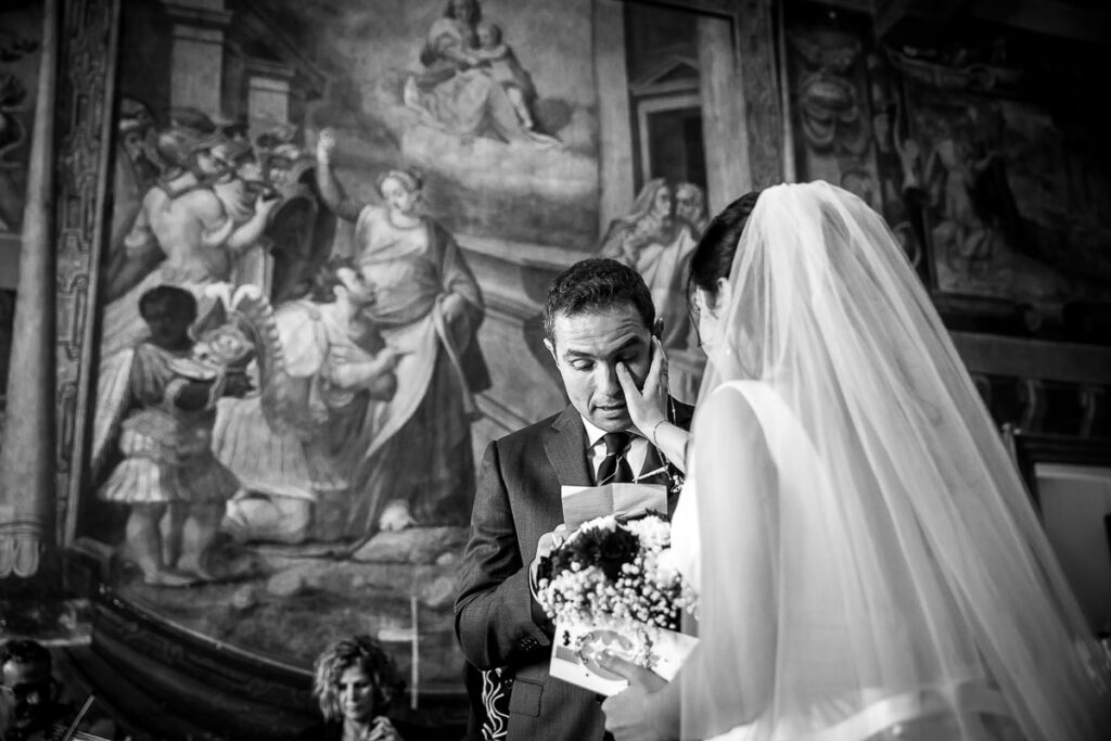 the bride wipes the tears of emotion of the groom during a wedding in rome while he is reading kind words to her