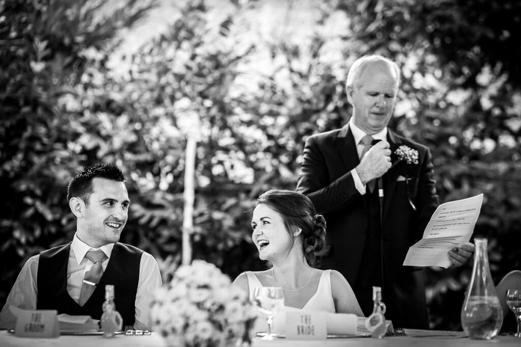 bride and groom at wedding reception dinner table during bride father speech at villa eva in ravello