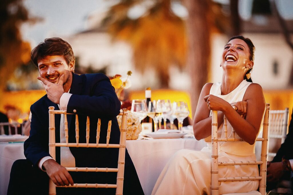 bride and groom laughing at the dinner table during wedding reception in rome after the wedding they spent kind words to the wedding photographer and acted as strong testimonials of wedding photographer work