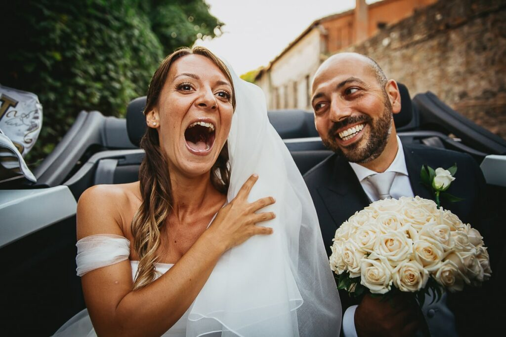 bride and groom having fun together in a cabriolet car after wedding ceremony