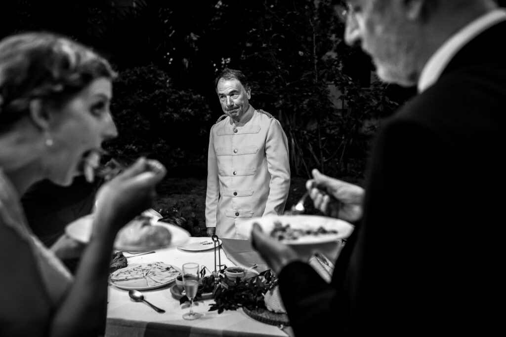 an wedding waiter is annoyed while the bride and her father are eating food