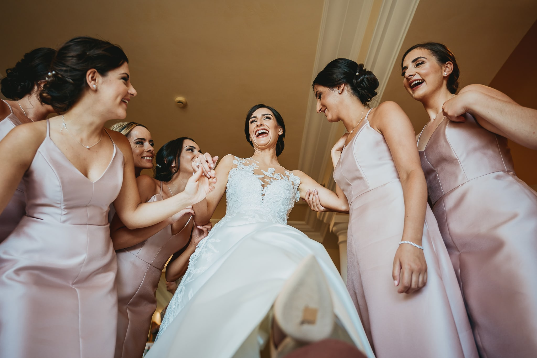 wedding photographers rome bride laughing with bridesmaids while getting dressed