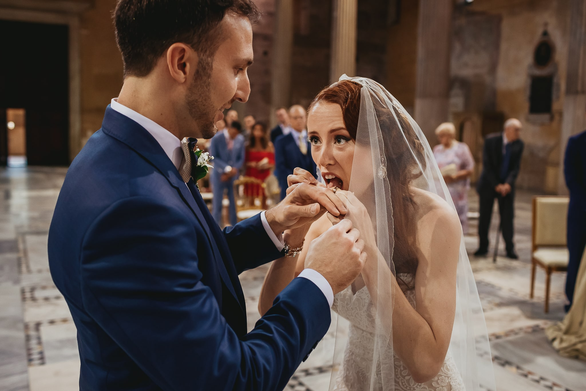 funny photo made by wedding photographers in rome of the bride licking the wedding ring before the exchange of the rings