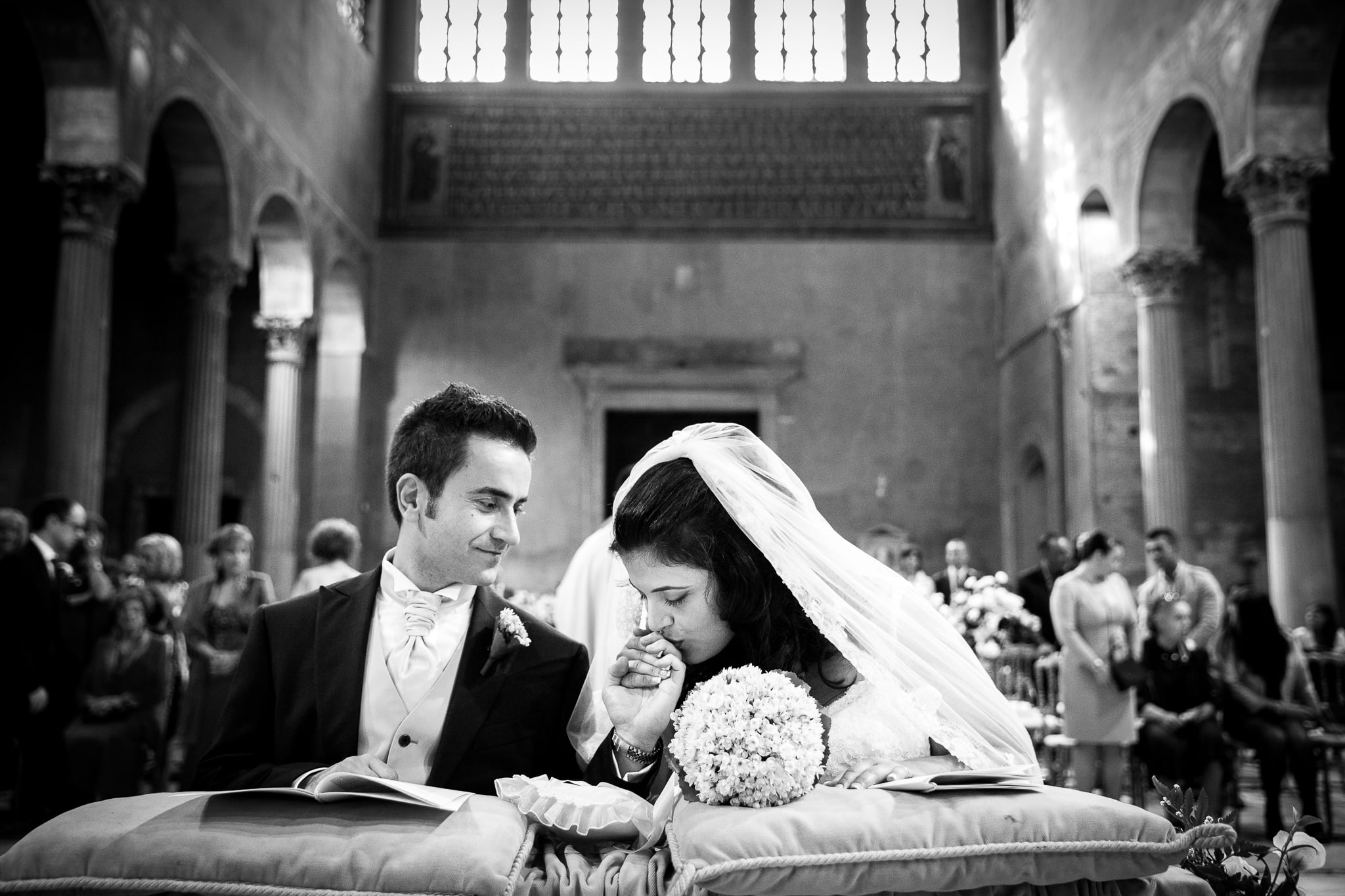 wedding photography info and prices bride kisses the groom hand in the church after the exchange of rings