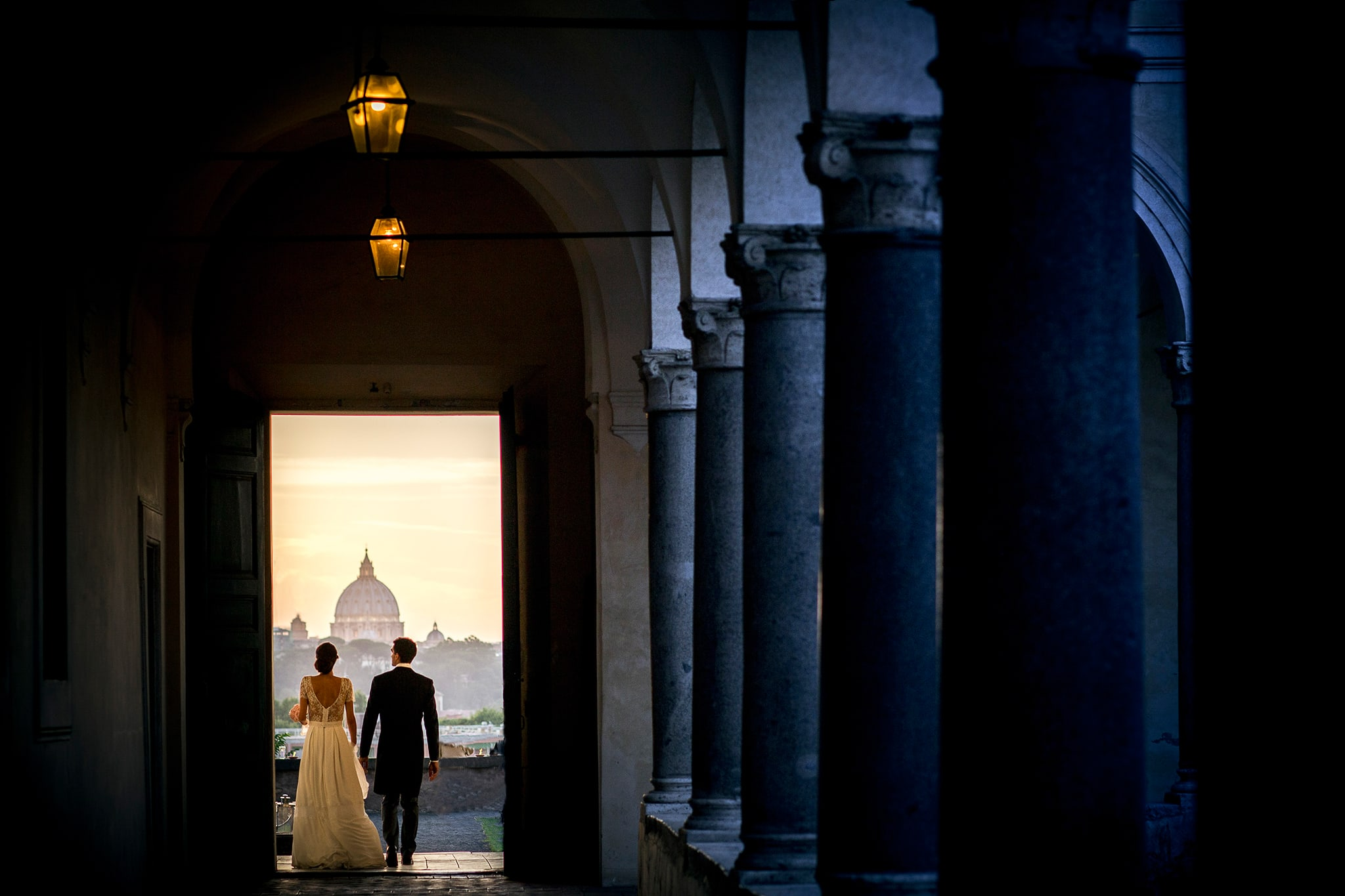 bride and groom holding hands in the cloister of the istituto studi romani with rome in the background image captured by the best wedding photographer in rome