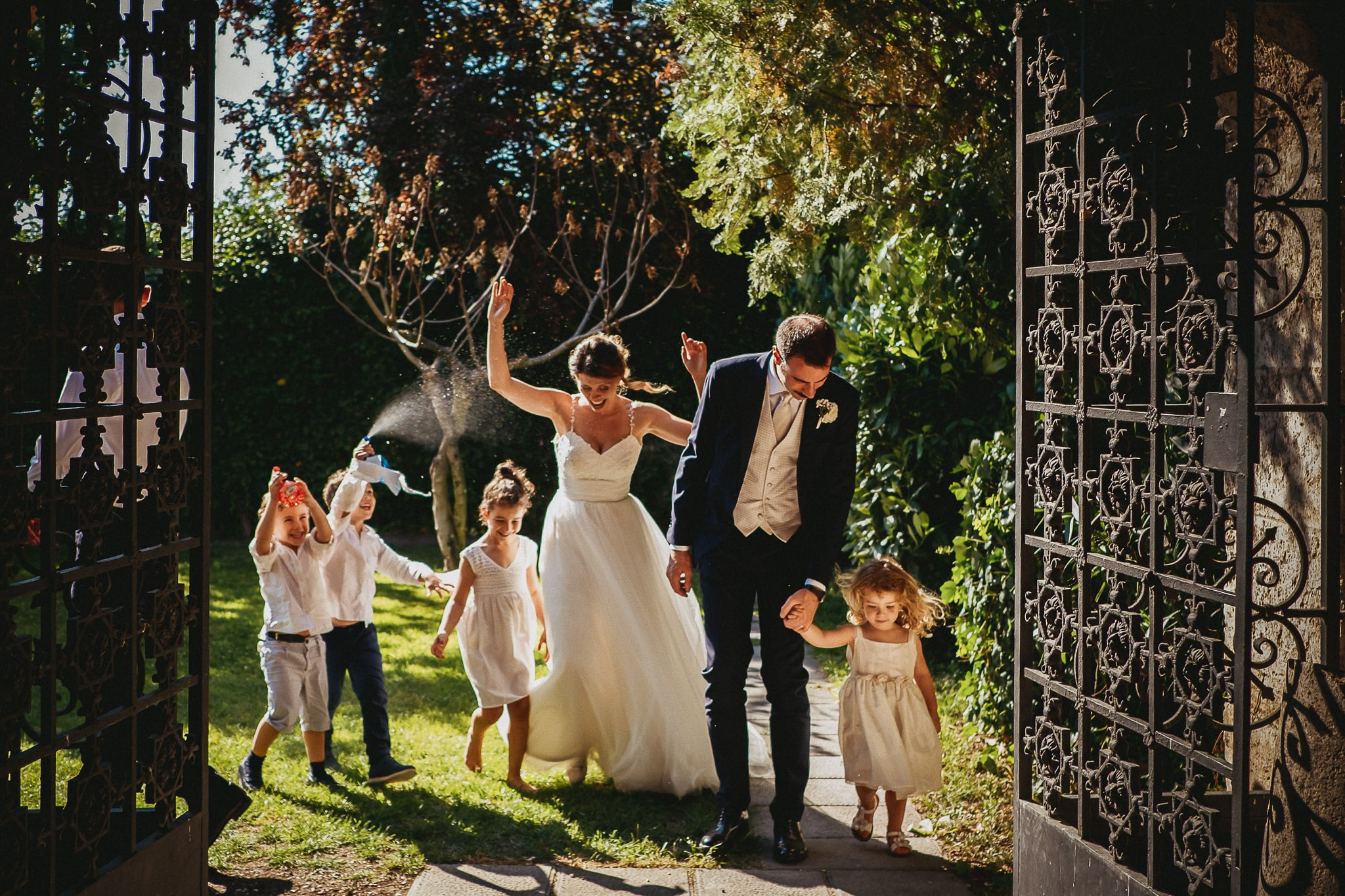newlyweds with children and water guns in a photo of the best wedding photographer in rome