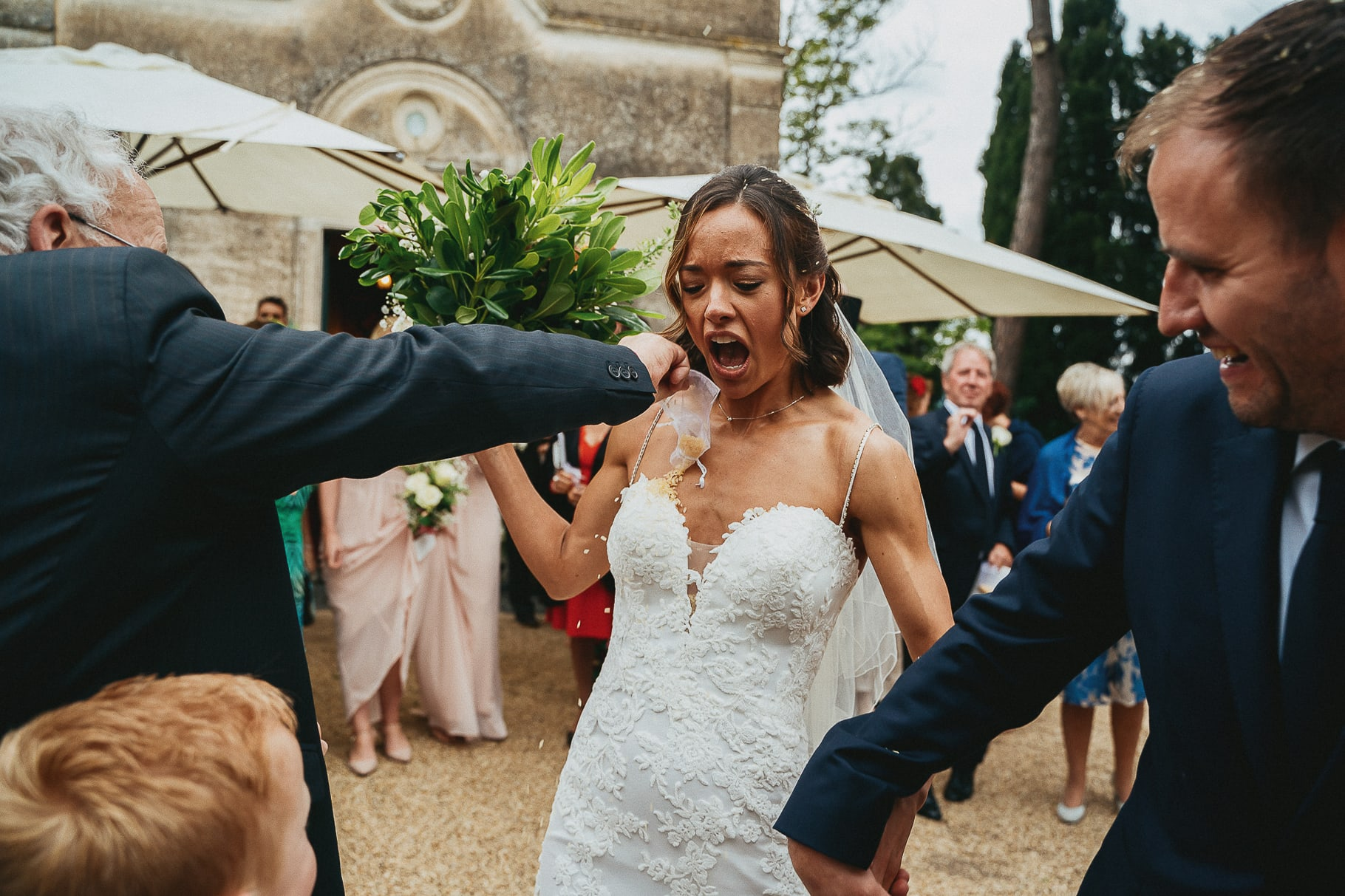 the bride and groom leave the church hand by hand and the guests throw rice in a photo captured by the wedding photographer italy