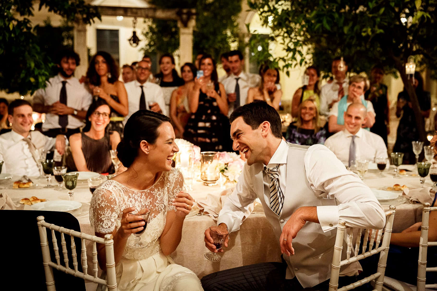 the bride and groom laugh and toast with the guests during the wedding reception in Rome