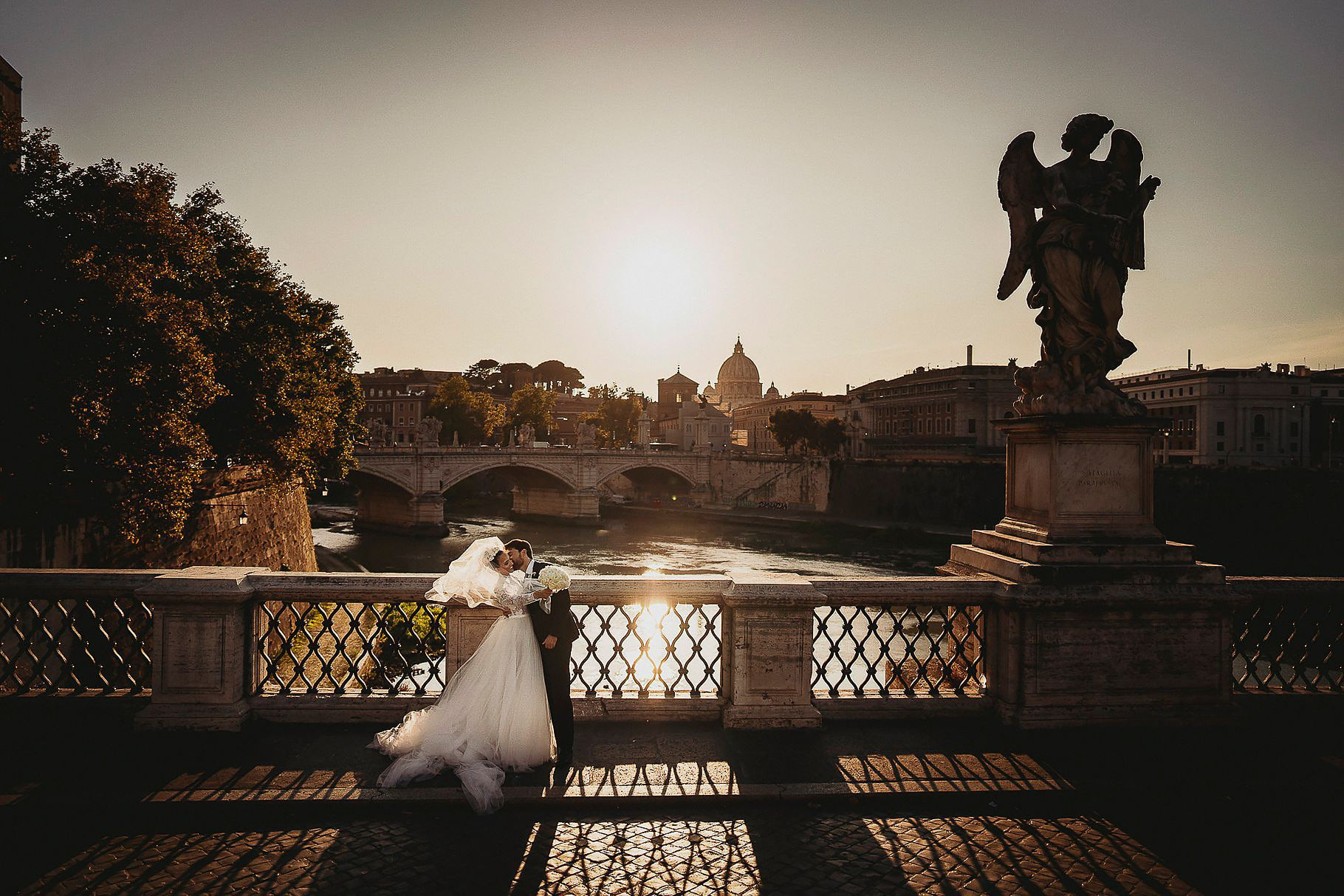 bridal couple photographed by the wedding photographer Italy on the ponte dell'angelo in rome with the tiber and st. peter dome in the background