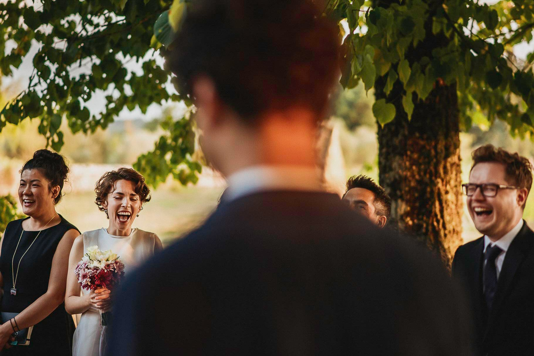 wedding photographer italy captured the spouses and witnesses laughing during the symbolic ceremony of an outdoor wedding