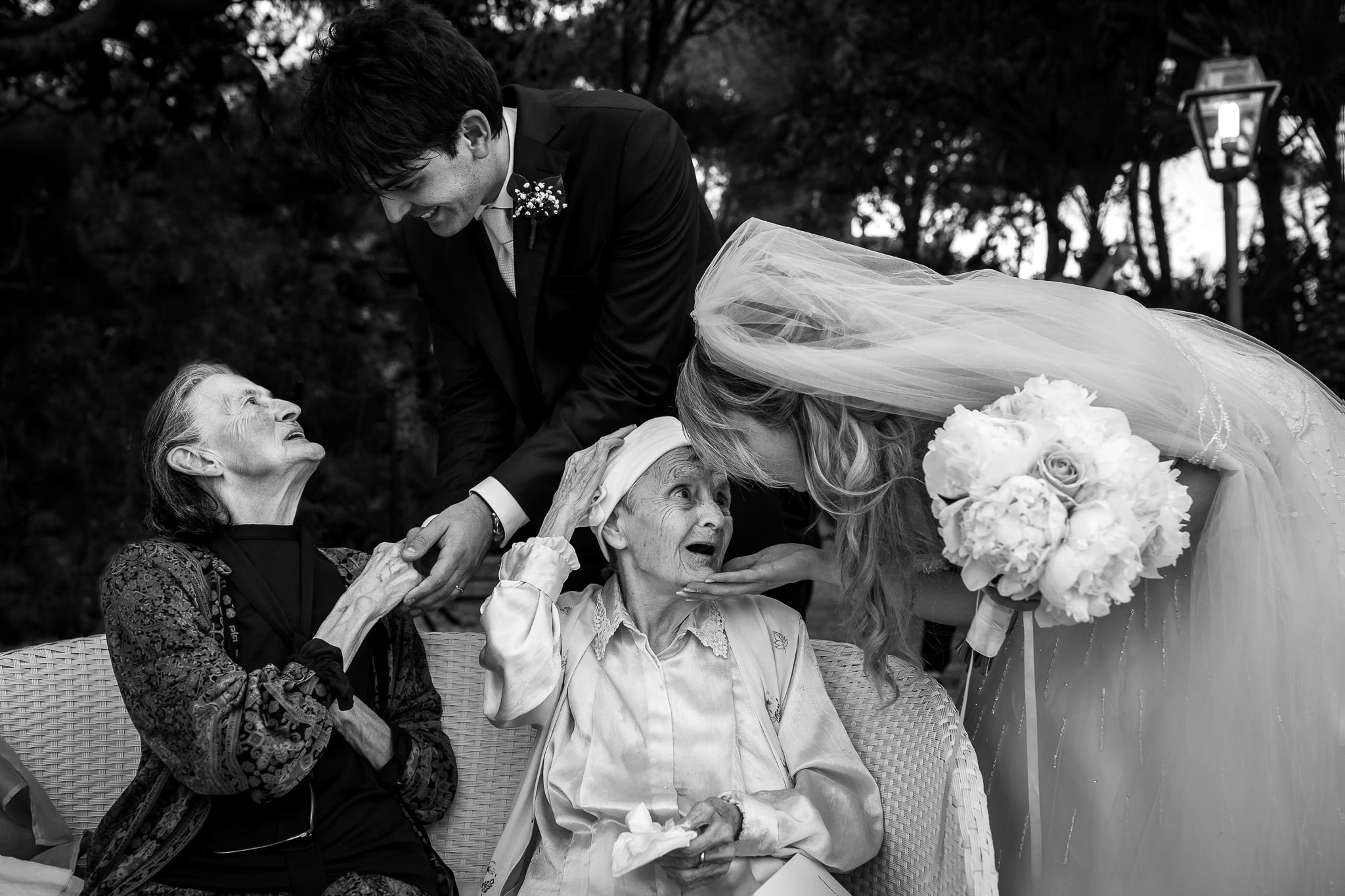 married couple greeting their grandmothers in a photo of the wedding photographer rome