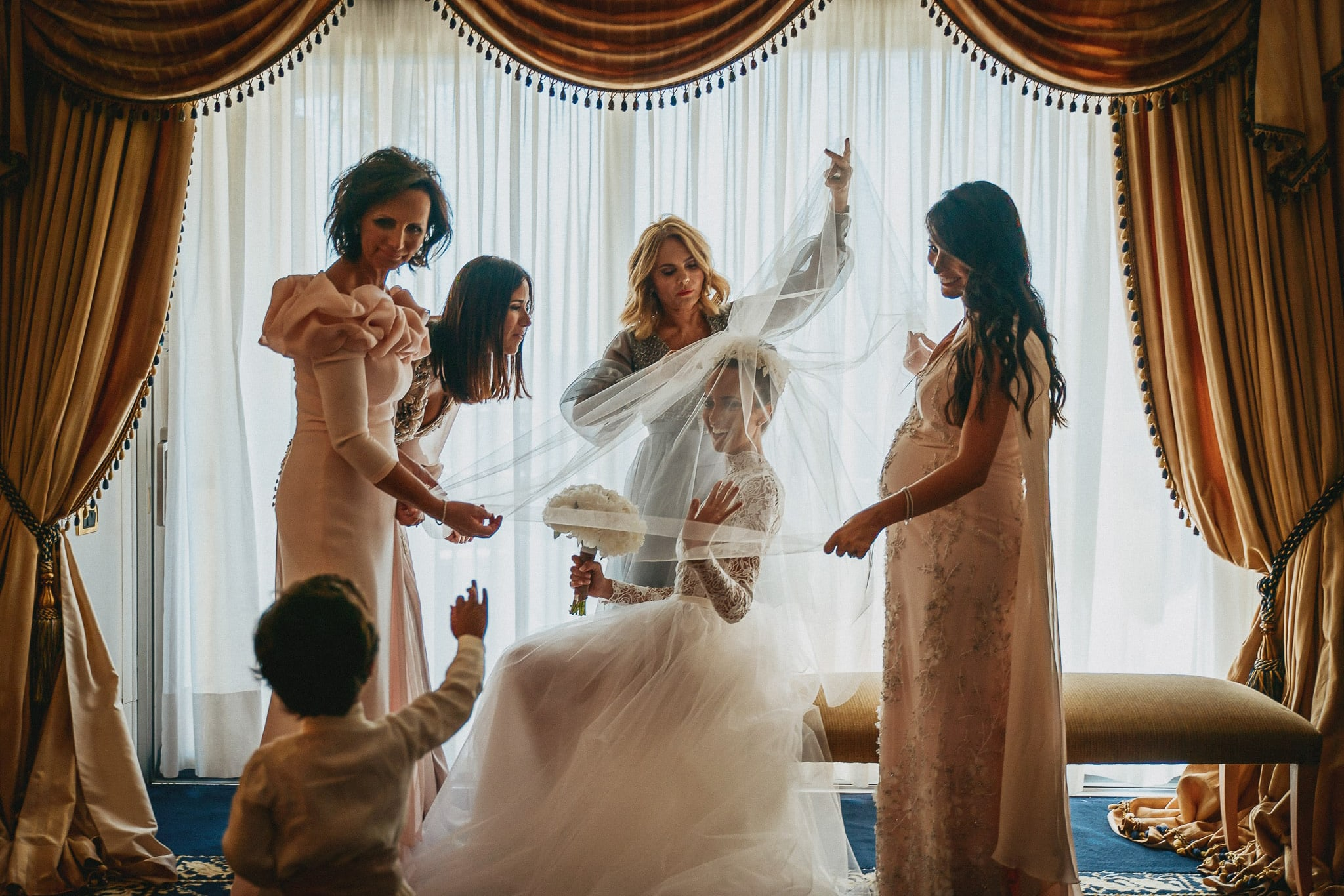 the bride wears a veil in a hotel room helped by her mother and bridesmaids before the wedding in Rome