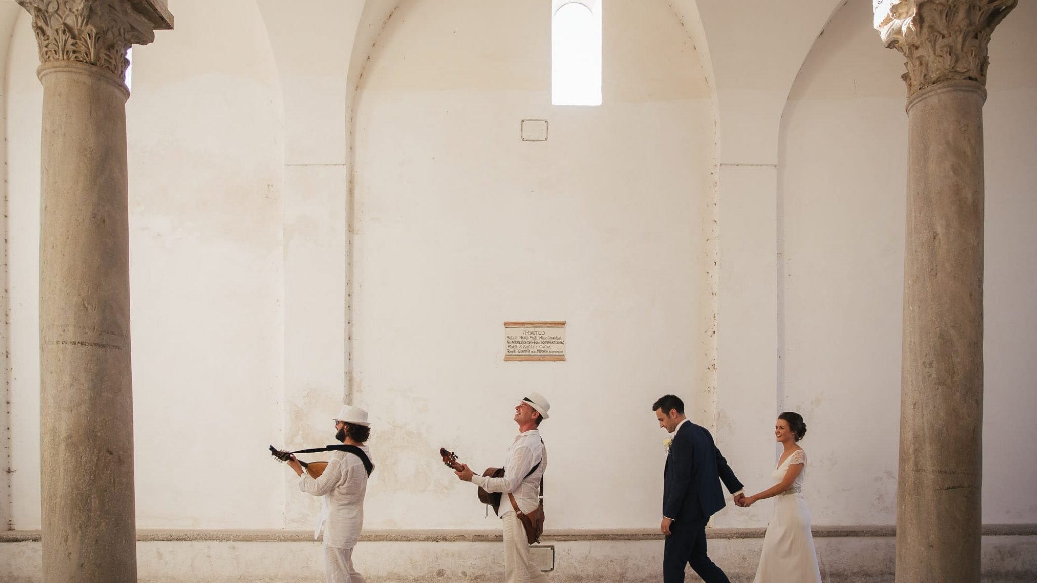 bride and groom walking hand in hand in the streets of ravello with the musicians
